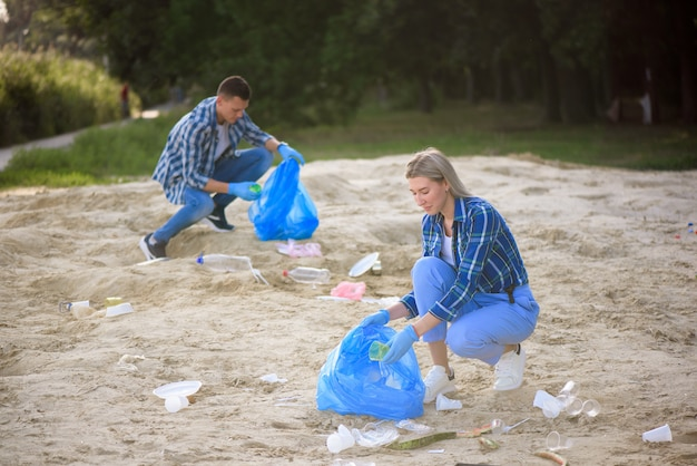 Happy volunteers with garbage bags cleaning area in park
