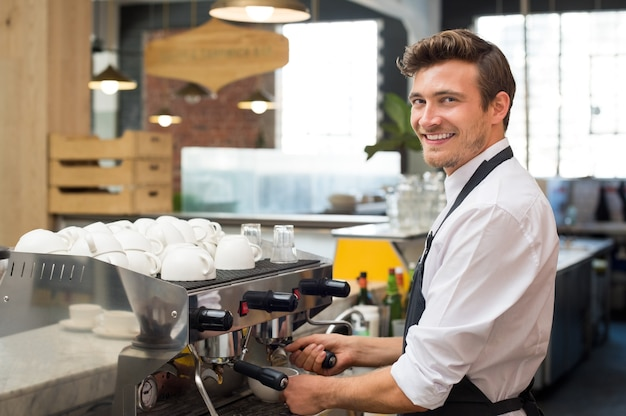 Happy waiter making coffee in machine while looking at front