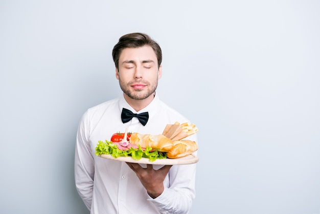 Happy waiter with closed eyes enjoying the aromatic smell of the dish on a tray