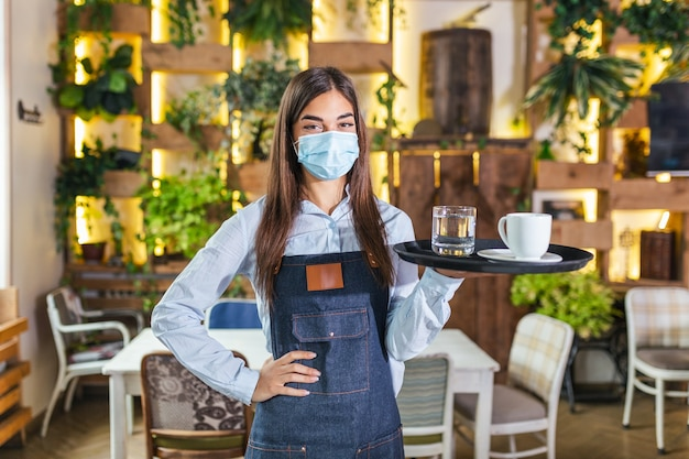 Happy waitress holding tray with cup of coffee, working in cafeteria and serves the table