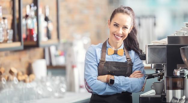 エプロンと木製の蝶ネクタイを着た幸せなウェイトレスが、コーヒーメーカーの隣に自信を持って立っています。