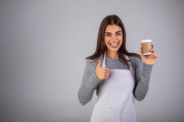 격리 된 카메라 앞에 서있는 동안 뜨거운 커피와 함께 유리를 제공하는 앞치마에 행복한 웨이트리스