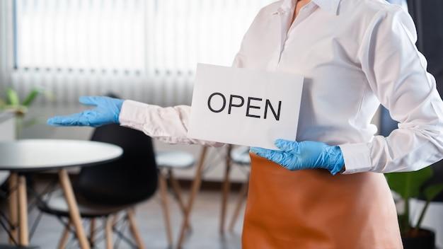 Счастливая официантка с защитной маской для лица держит открытую табличку для открытия в своем ресторане