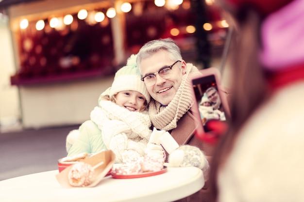 행복합니다. 아빠와 함께 카메라에 포즈를 취하는 동안 행복을 느끼는 즐거운 소녀