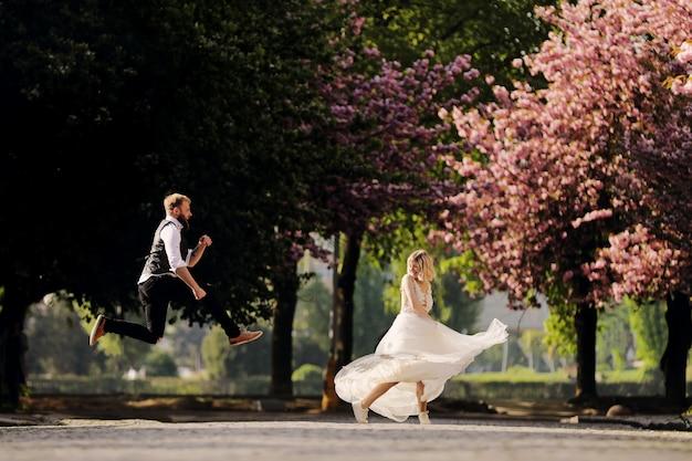 幸せな結婚式のカップルは、春の満開の桜公園で楽しんでいます。ひげを持つ男はジャンプ、長いドレスを着た女性はダンスです。公園で新婚カップル。新婚。素朴な結婚式。