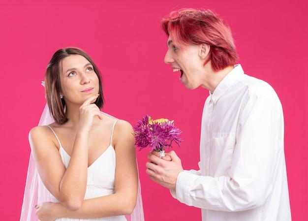행복한 결혼 커플 신랑과 신부 행복하고 쾌활한 신랑이 핑크색 벽 위에 서 있는 웨딩 드레스를 입고 웃는 신부를 위해 꽃을 주고 있습니다.