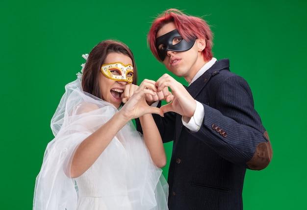 仮面舞踏会のマスクを身に着けているウェディングドレスの幸せな結婚式のカップルの新郎と新婦は、緑の壁の上に立って一緒に指でハートジェスチャーを作る幸せで自信を持っています