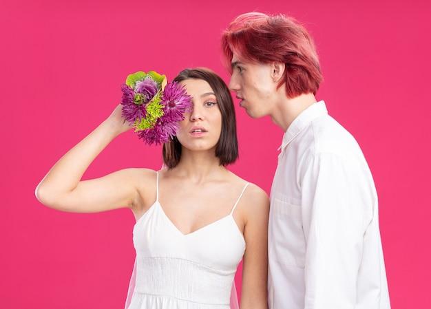一緒に楽しんでいる花とウェディングドレスで幸せな結婚式のカップルの新郎と新婦