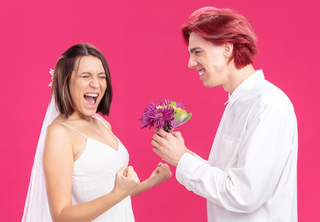 Happy wedding couple groom and bride happy and cheerful groom giving flowers for his excited bride in wedding dress standing on pink