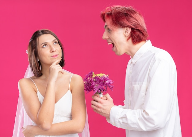 Happy wedding couple groom and bride happy and cheerful groom giving flowers for his smiling bride in wedding dress standing over pink wall