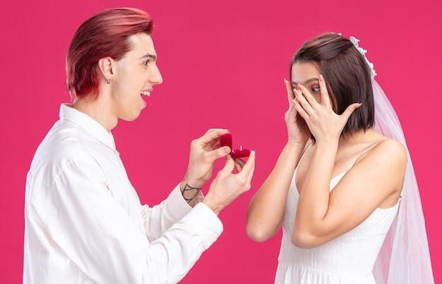 Felice coppia di sposi di sposo e sposa che fa proposta con l'anello nuziale in una scatola regalo felice ed eccitato in piedi sul rosa