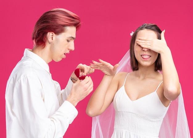 Felice sposi di sposo e sposa uomo che fa proposta con fede nuziale in una scatola regalo mentre la sposa in abito da sposa copre i suoi occhi felice ed eccitata