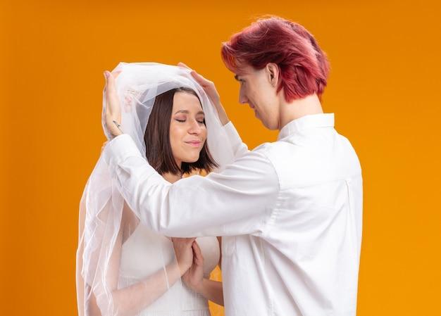 Felice sposi sposo e sposa in abito da sposa sotto il velo, lo sposo che dà un primo sguardo alla sua sposa