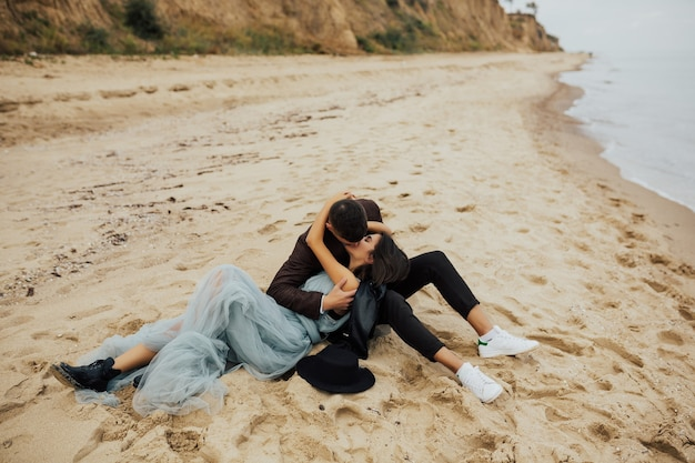 幸せな結婚式のカップルは、海の近くの砂浜に横たわってキスしています。