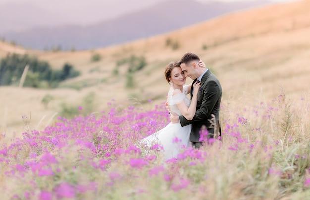 幸せな結婚式のカップルはピンクの花で囲まれた牧草地の丘の上に座っています。