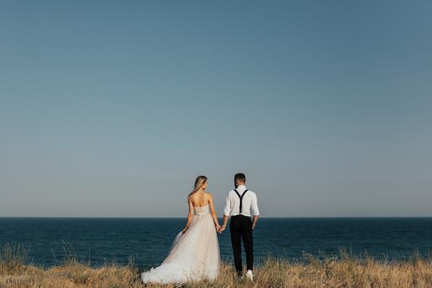 海のビーチで幸せな結婚式のカップル。