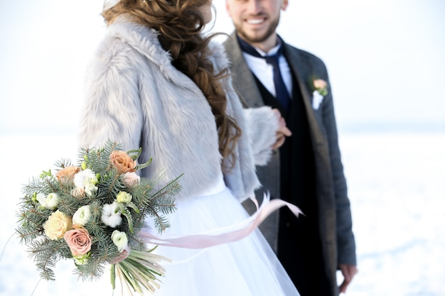 Happy wedding couple outdoors on winter day, closeup