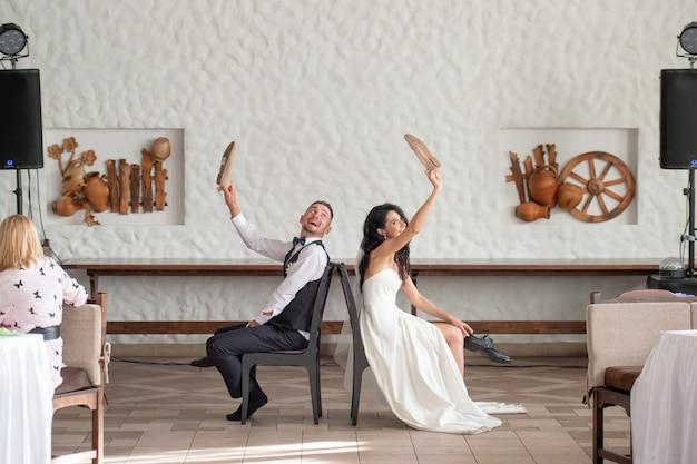 レストランで面白いスラヴの伝統を通過する幸せな結婚式のカップル