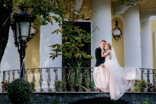 Happy wedding couple poses on the balcony before a house with white pillars Premium Photo