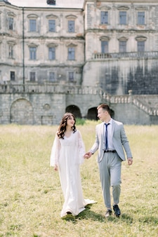 Happy wedding couple standing and walking near old ancient castle