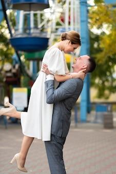 Счастливая свадебная фотография жениха и невесты на фоне колеса обозрения