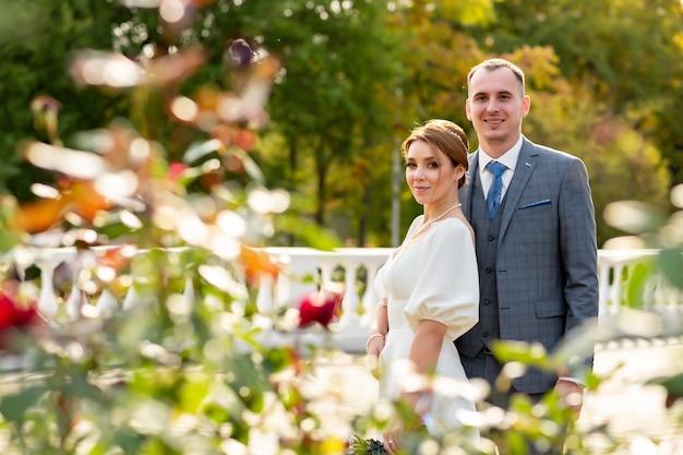 Счастливая свадебная фотография жениха и невесты, смотрящих в камеру