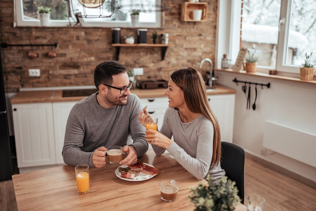 Happy weekend. positive millennial couple sitting in the modern rustic kitchen, drinking morning coffee and having breakfast.