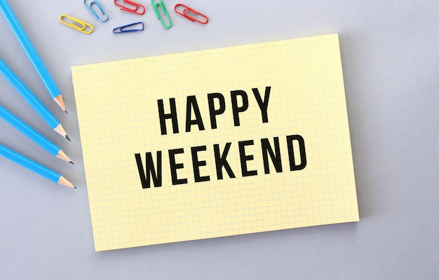 Happy weekend text in notebook on gray background next to pencils and paper clips.