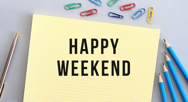 Happy weekend text in notebook on gray background next to pencils, pen and paper clips. concept.