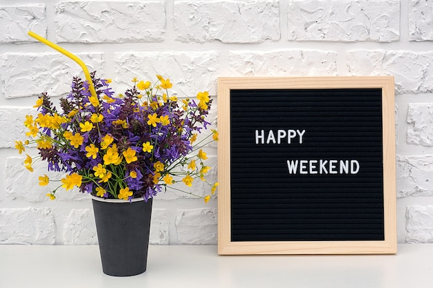 Happy weekend words on black letter board and bouquet of yellow dandelions flowers