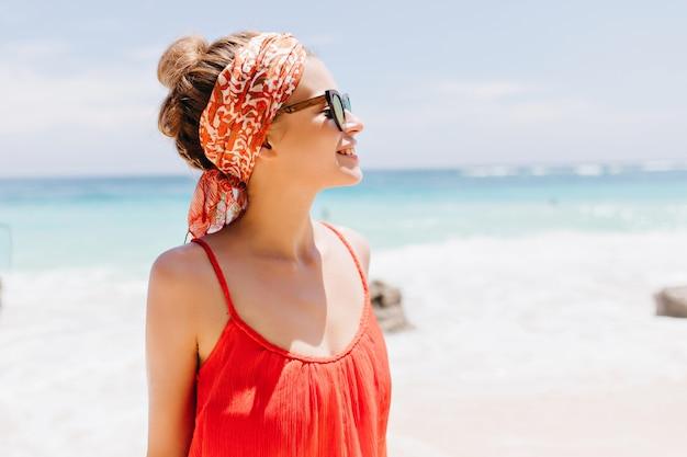 Felice modello femminile bianco con nastro rosso in posa. colpo esterno di elegante ragazza alla moda in occhiali da sole sorridente durante la passeggiata lungo la costa dell'oceano.