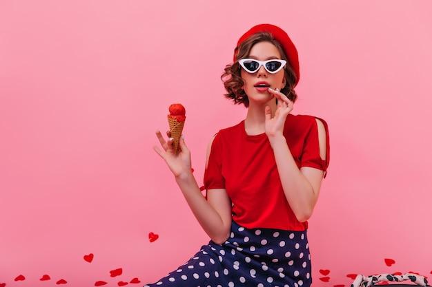 아이스크림을 먹는 우아한 선글라스에 행복 한 백인 여자. 차가운 디저트를 즐기는 아름다운 프랑스 여성 모델.