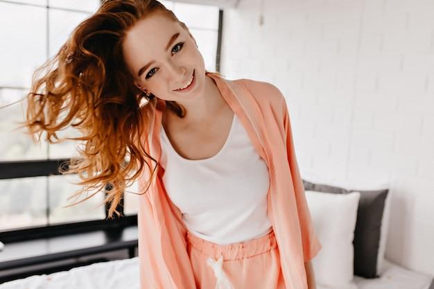 巻き毛の笑顔で幸せな白人の女の子。家で楽しんでいるインスピレーションを得た赤毛モデル。