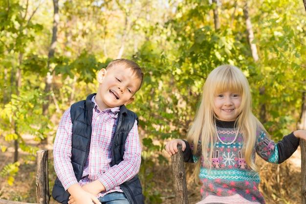 Счастливые белые маленькие дети в осеннем модном наряде посещают лес в осенний сезон. снято с зелеными деревьями на заднем плане.
