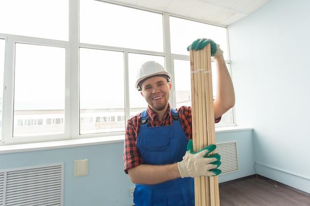 Счастливый белый мужчина-строитель, держа деревянные доски в перчатках.