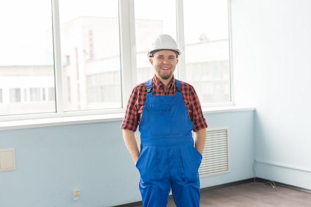 Счастливый белый мужчина-строитель перед окном,