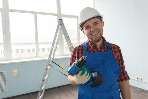 Счастливый белый мужчина-строитель с отверткой перед лестницей, в белом шлеме.