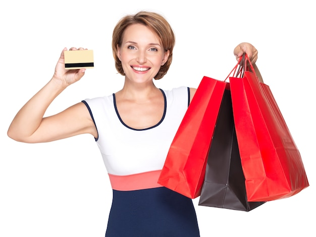 Happy white woman with purchasing and credit card over white wall