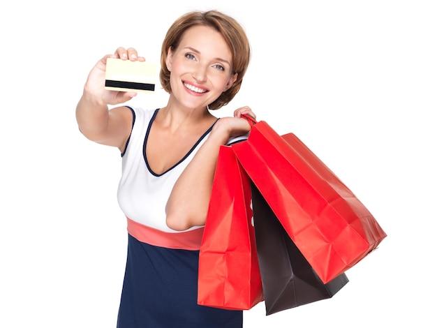 쇼핑백과 흰 벽에 신용 카드와 함께 행복 한 백인 여자