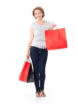 Felice donna bianca con borse della spesa su bianco