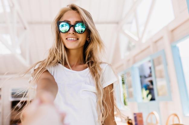 Felice donna bianca con abbronzatura in posa nella caffetteria. ritratto dell'interno del modello femminile caucasico sveglio con bei capelli biondi.