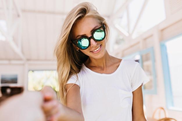 선탠 카페테리아에서 포즈와 함께 행복 한 백인 여자. 아름다운 금발 머리를 가진 귀여운 백인 여성 모델의 실내 초상화.