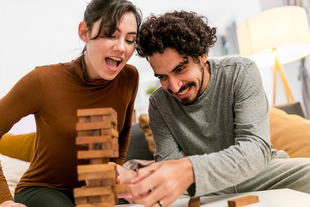 Happy wife and husband playing a wooden tower game