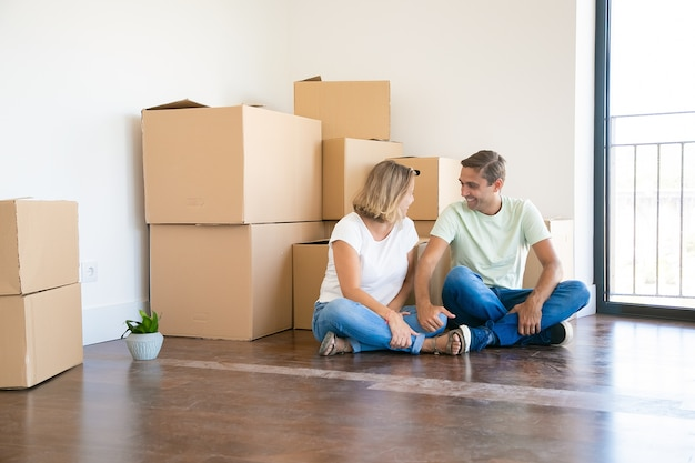 Happy wife and husband sitting cross-legged on floor in new apartment near cardboard boxes