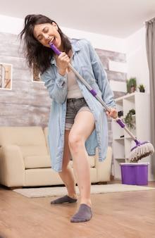 Счастливая жена поет на швабре во время работы по дому