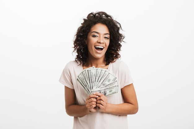 Happy winner american woman with afro hairstyle and big smile holding money prize dollar cash, isolated over white wall
