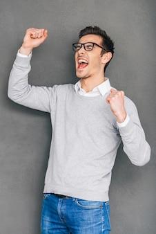 幸せな勝者。立っている間、身振りで示すと彼の口を開いたままにしておく陽気な若い男