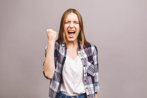 Happy winner! close-up of emotional young attractive woman with keeping hands in fists, isolated on grey wall. surprised young woman shouting.