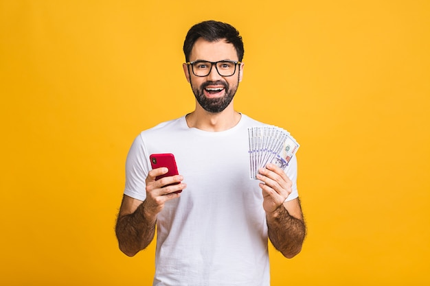 Happy winner! excited young bearded man in casual holding lots of money in dollar currency and cell phone in hands isolated over yellow wall.