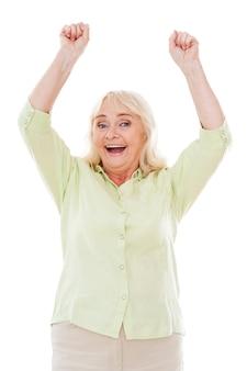 행복한 승자. 흰색 배경에 격리된 채 팔을 들고 카메라를 바라보는 행복한 노년 여성